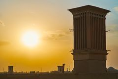 Sunset in old Yazd, Iran. Enjoy romantic sunset over the roofs of historic Fahadan district with a view on medieval badgirs windcatchers and fiery sky, Yazd stock image