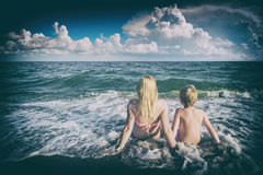Enjoy the seascape. Instagram stylisation. Mother with son sitting on sandy beach in a water and enjoy the seascape. Instagram stylisation Royalty Free Stock Images