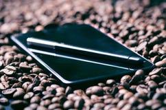 enjoy Stylus pióro na mądrze telefonie surowym kawowym tle i Energia surowa fasoli kawa zebrać Naturalny tło Lif Zdjęcie Stock