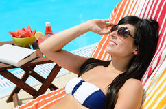 Enjoy Summer. Woman sunbathing in a resort with sunglasses and a book in a table at the poolside Stock Photography