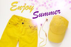 Yellow flatlay jeans, baseball cap and headphones on white background card,top view. Enjoy Summer card background