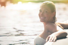 Enjoy the summer. Woman relaxing in the pool water. A beautiful woman with big smile in water in a swimming pool. Relaxation and peace. Against the side of the royalty free stock photography