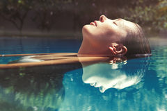 Enjoy the summer. Woman relaxing in the pool water. A beautiful woman floating in water in a swimming pool. Relaxation and peace. Eyes closed and wellness