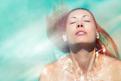Enjoy the summer. Woman relaxing in the pool water. A beautiful woman floating in water in a swimming pool. Relaxation and peace. Eyes closed and wellness Stock Images