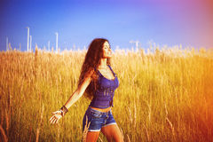 Enjoy in sun and nature. Smiling beautiful woman with long curly hair enjoy in sun and nature  in grass field Royalty Free Stock Images