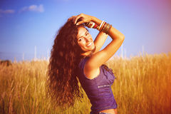 Enjoy in sun and nature. Smiling beautiful woman with long curly hair enjoy in sun and nature  in grass field Stock Images