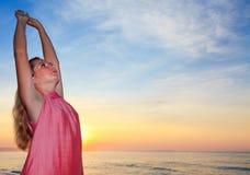 Enjoy sunrise. Young woman enjoy sunrise on the beach Stock Photography