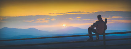 Enjoy sunrise in mountain valley. Instagram stylisation. Man sitting on a wooden fence and enjoy sunrise in mountain valley. Instagram stylisation Royalty Free Stock Photos