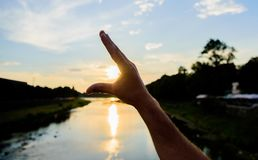 Enjoy sunset above river surface. River sun reflection. Catch last sunbeam. Male hand pointing at sun in blue sky at. Evening time admire landscape. Capture stock photo