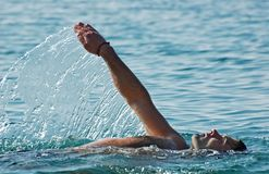 Enjoy swimming!. Relaxed young man swimming in a pure and clear sea water making nice water splashes Royalty Free Stock Photo