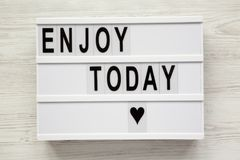 `Enjoy today` word on lightbox over white wooden background, fro. M above. Top view, overhead, flat lay. Closeup stock images
