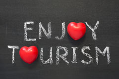 Enjoy tourism. Phrase handwritten on school blackboard Royalty Free Stock Image