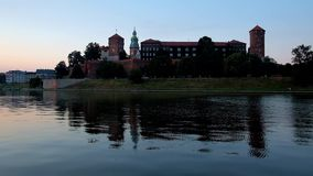 Enjoy the twilight by Vistula river, Poland. Romantic evening walk along the riverside park in Krakow with a view on Wawel Castle and its clear reflection in stock video