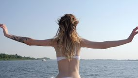 Enjoy vacation on yacht into summer season, rear view girl in swimsuit raises hands up. In slow motion stock video footage