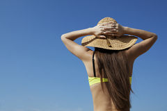 Enjoy vacations moment. On the beach. Attractive young woman in the sun hat and bikini standing on the blue sky background Royalty Free Stock Photography