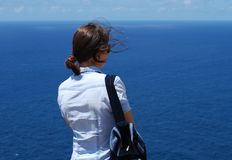 Enjoy The View. The girl enjoys the view of Caribbean Sea standing on the edge of Antigua island coast Royalty Free Stock Photos