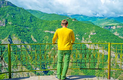 Enjoy the view. The man stands on the cliff's edge and enjoys the view of Vorotan river gorge with rocky slopes, covered with greenery, Halidzor, Syunik Province Royalty Free Stock Photography