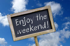 Enjoy the weekend. A chalkboard on a blue sky background with the text Enjoy the weekend vector illustration