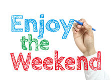 Enjoy the Weekend. Man is writing text Enjoy the Weekend with marker on transparent wipe board Stock Photo