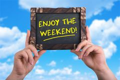 Enjoy the weekend. A woman holding chalkboard with words enjoy the weekend isolated on blue sky background stock photo