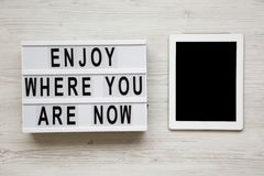 `Enjoy where you are now` words on lightbox, tablet with blank screen over white wooden background, overhead view. Top view, flat. Lay, from above royalty free stock images