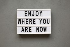 `Enjoy where you are now` words on modern board over concrete background, top view. Flat lay. From above royalty free stock images