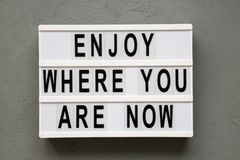 `Enjoy where you are now` words on modern board over grey background, top view. Flat lay, from above. Closeup royalty free stock photography
