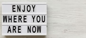 `Enjoy where you are now` words on modern board over white wooden surface, overhead. Space for text.  royalty free stock image