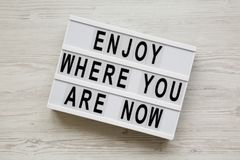 `Enjoy where you are now` words on modern board over white wooden surface, overhead view. Flat lay, from above.  royalty free stock images