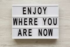 `Enjoy where you are now` words on modern board over white wooden surface, top view. Close-up.  royalty free stock photos