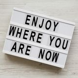 `Enjoy where you are now` words on modern board over white wooden surface, top view. Flat lay, from above.  royalty free stock image