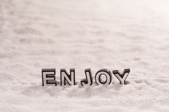 Enjoy word on white sand. Enjoy word silver and black on shiny white sand Stock Image