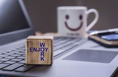 Enjoy work text on laptop. Wooden block with Enjoy work text on laptop keyboard with happy face mug background Royalty Free Stock Photo