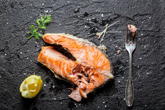 Enjoy your fresh fried salmon. On black rock Stock Photography