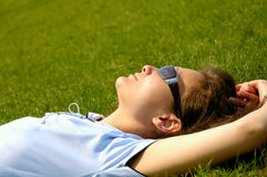 Enjoy your life. Happy young woman lying on grass relaxing looking at the sky stock images