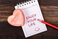 Enjoy your life handwritten. On a notebook with heart and red pencil on wooden background Royalty Free Stock Photos