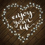 Enjoy your life. Quote typography over wooden background with realistic christmas lights, vector illustration Stock Photo