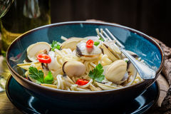 Enjoy your seafood pasta with clams, parsley and peppers. On old wooden barrel Stock Images