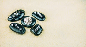 Enjoy your time off cube letters on black stones on sandy background Royalty Free Stock Photo