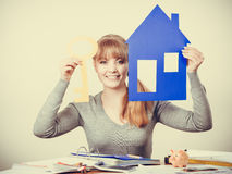 Enjoyable estate agent with house ang key. Selling and buying real estate concept. Young blonde smiling positive female estate agent ready to sell house home Stock Photo