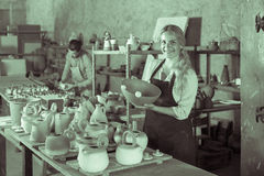 Enjoyable female artisan having ceramics in workshop. Enjoyable female artisan having ceramics in hands and standing in workshop Royalty Free Stock Photo
