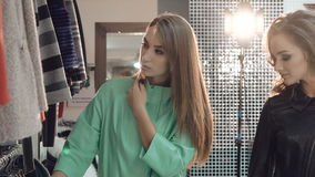 Enjoyable lady choosing the coats in boutique stock video footage