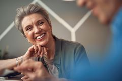 Happy smiling aged lady looking to her friend. Enjoyable meeting. Close up portrait of cheerful aged women looking with pleasure to her male friend while sitting stock photography