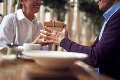 Aged man giving present box to happy lady. Enjoyable meetings. Close up cropped head portrait of happy aged women being pleased and surprised of taking present royalty free stock image