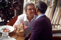 Happy woman gratefully kissing man for present. Enjoyable meetings. Close up portrait of happy elegant lady with closed eyes gratefully kissing male friend for stock photos