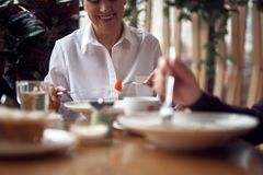 Smiling woman eating salad in cafe with man. Enjoyable meetings. Close up selective focus on aged happy lady eating salad in cafe while having meeting with male royalty free stock photos