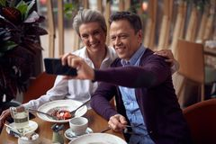 Happy aged lady and man making selfie in cafe. Enjoyable meetings. Waist up portrait of happy smiling aged elegant women and gentleman making selfie on royalty free stock image