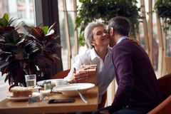 Elegant woman gratefully kissing man for present. Enjoyable meetings. Waist up portrait of pleased elegant lady gratefully kissing mature male friend for present stock photography