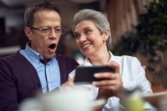Shocked mature man look at smth in mobile phone. Enjoyable meetings. Waist up portrait of shocked aged men looking at something interesting in mobile phone stock photography