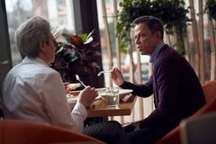 Aged man and woman talking while having dinner. Enjoyable meetings. Waist up side on portrait of mature male and female having dinner in cafe and discussing royalty free stock photo